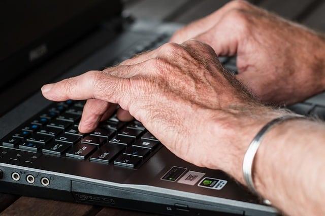 senior writing real laptop